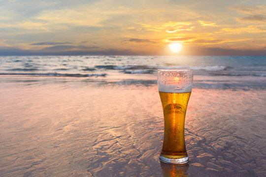 Glass of cold beer on the sea shore at the sunset. Relax on the beach.