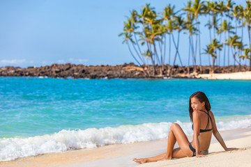 Beach bikini summer holiday hawaii vacation woman travel lifestyle. Asian girl relaxing enjoying sun on holidays.