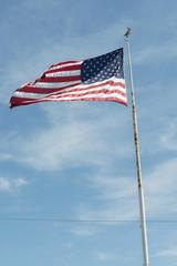 waving American flag on a white pylon against blue sky