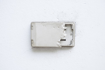 Electric plug cover was dog bite. Wall cover plug socket damage. Outdoor electric outlet on white wall.