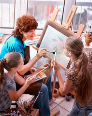 Artist painting easel in studio. Authentic grandmother and kids girl paints with palette watercolor paints palette and brush sunlight. Students taught older woman draw. Elderly professional artist.