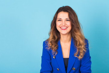 Close up portrait of a beautiful young woman smiling on blue background