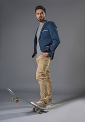 Full length portrait of standing attractive businessman skateboarding with focused look and hands in pockets