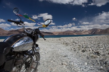 Vintage motorcycle on background of beautiful mountain lake. Pangong lake in Ladakh by vintage motorcycle. Offroad trail leading to highland lake with vintage motorcycle. Version 2.