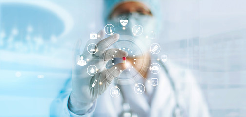 Medicine doctor holding a color capsule pill in hand with medical icons network connection on modern virtual screen interface in laboratory background, medical technology network concept