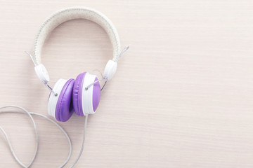 Purple and white headphone on wood table with free space for background. Music relax concept.
