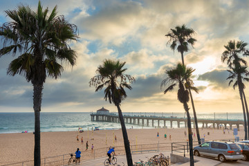 Palm trees and Pier at sunset in Manhattan Beach. Fashion travel and tropical beach concept.