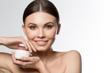 Portrait of happy girl holding jar of cosmetic product for skin treatment. She is looking at camera and smiling. Isolated and copy space