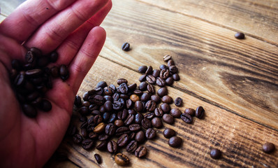 coffe beans in men hand on wooden background
