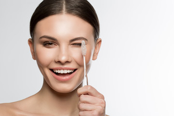 Portrait of excited young woman holding a toothbrush near her eye and laugh. Beauty and hygiene concept. Isolated and copy space