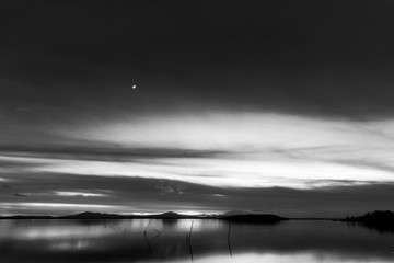 Beautiful view of Trasimeno lake (Umbria, Italy) at dusk, with black and white tones and moon in the sky