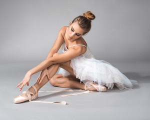 Graceful ballerina sitting and untying her training shoes with calmness