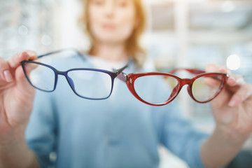 Close up female hands holding eyeglasses in glasses shop. Ophthalmology concept
