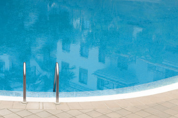 Outdoor swimming pool in curved shape with stair at sunny day.  Hotel reflection in blue water . Relax and vacation concept.