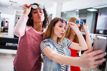 Three young stylish girlfriends raising fashionable sunglasses while taking selfie with smartphone in shopping mall