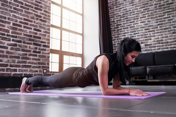 Young sportswoman working-out at home doing plank exercise on yoga mat