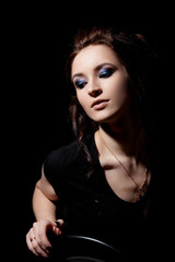 Girl in black T-shirt and with make-up sits on chair and looks down on black background close-up