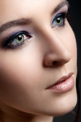 Portrait of a stylish girl with a professional make-up and clean skin on a black background close-up