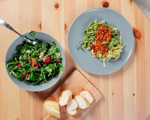 Fetuchini pasta with beef tomato sauce on wood table , italian food.  arugula salad