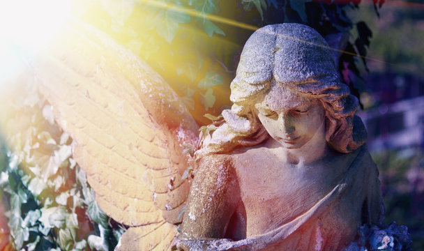 Close up of an ancient statue of guardian angel (vintage style photo)