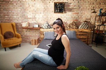 Happy pregnant woman sitting on bed at home