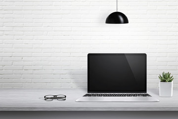 Wall Mural - Modern laptop computer on desk with blank screen for mockup. White brick wall in background with free space for text.