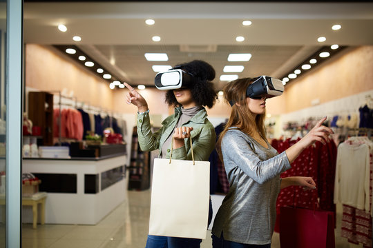 Two women in modern virtual reality headsets having expirience in shopping at lingerie store. Multiracial girls in vr glasses with bags touching and pointing interface elements in underwear shop.