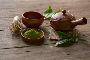 Matcha Green Tea and Japanese tea set. Ceramic teapot and a steaming cup on wooden background