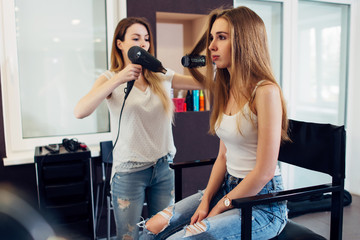 Professional hairstylist using hairdryer and round brush to style long fair hair of the female customer in beauty salon
