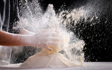 Making dough by female hands at home in kitchen