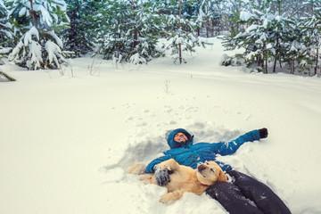 Best friends. Happy man with Labrador retriever dog lying in snowy winter forest. Man enjoying snow