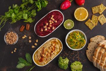 Vegan food background. Vegetarian snacks: hummus, beetroot hummus, green peas dip, vegetables. Top view, dark background, copy space.