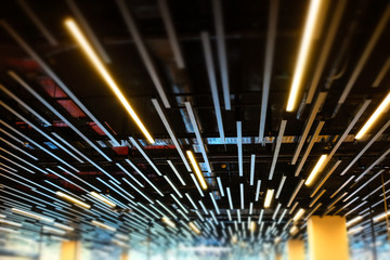 Fluorescent lamps line in modern building ceiling