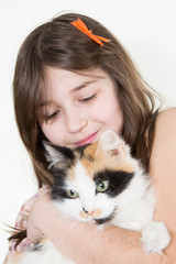 Caucasian little girl holds her cat in the arms and look
