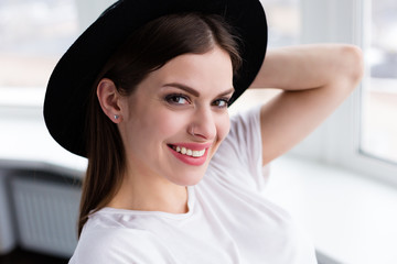 Beautiful happy woman sitting by the window