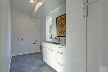 White laundry room interior with cabinets and gray tiled floor.
