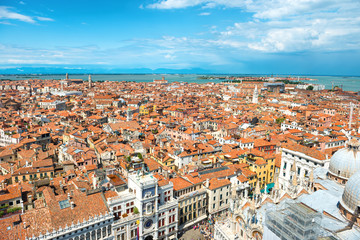 Aerial view on Venice roofs, houses, sea and people on square from San Marco tower