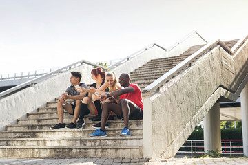 Young runners in the city sitting on the stairs.