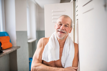 Senior man standing by the lockers in an indoor swimming pool.