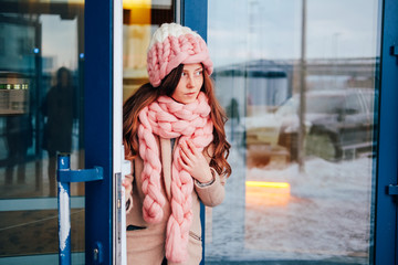 Cute young woman in knitted hat and scarf leaving the building