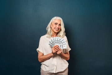 Cheerful mature old woman showing money.