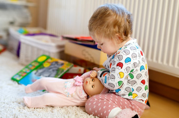 Cute adorable baby girl playing with first doll. Beautiful toddler child at home.