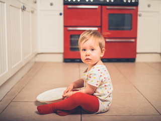 Little boy on kitchen floor with salad spinner