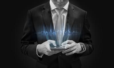 Businessman using mobile smart phone, with futuristic buildings hologram
