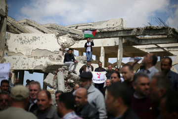 Palestinians take part in a protest against a decision by Palestinian authority to refer employees of Civil Aviation Authority into retirement, at the destroyed buildings of Gaza airport, in Rafah in the southern Gaza Strip