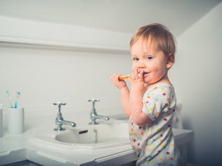 Little boy brushing his teeth by the sink