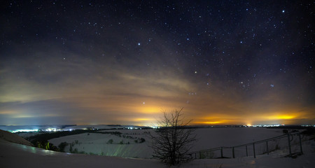 Stars of the night sky with clouds. Snowy winter landscape at dusk. Panoramic view of the valley at the hills.