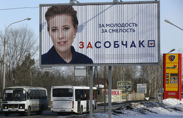 Buses drive past a board, which advertises the campaign of presidentia candidate Sobchak in Krasnoyarsk
