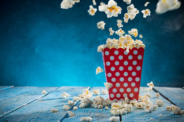 Box of popcorn on blue background.