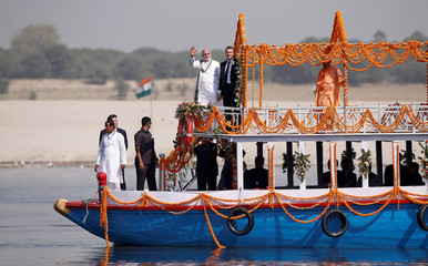 India's Prime Minister Narendra Modi, French President Emmanuel Macron and Chief Minister of India's most populous state of Uttar Pradesh, Yogi Adityanath pictured aboard a boat in Varanasi